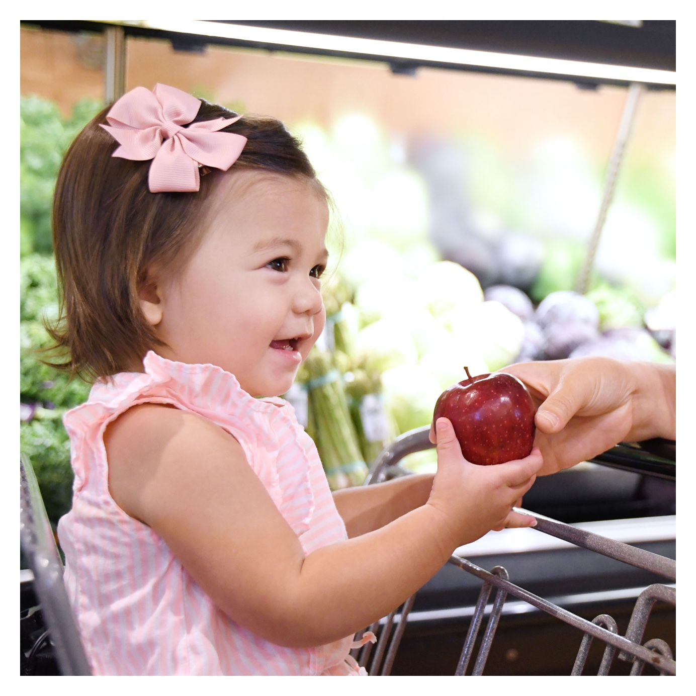 a little girl holding an apple in the Produce Department and smiling