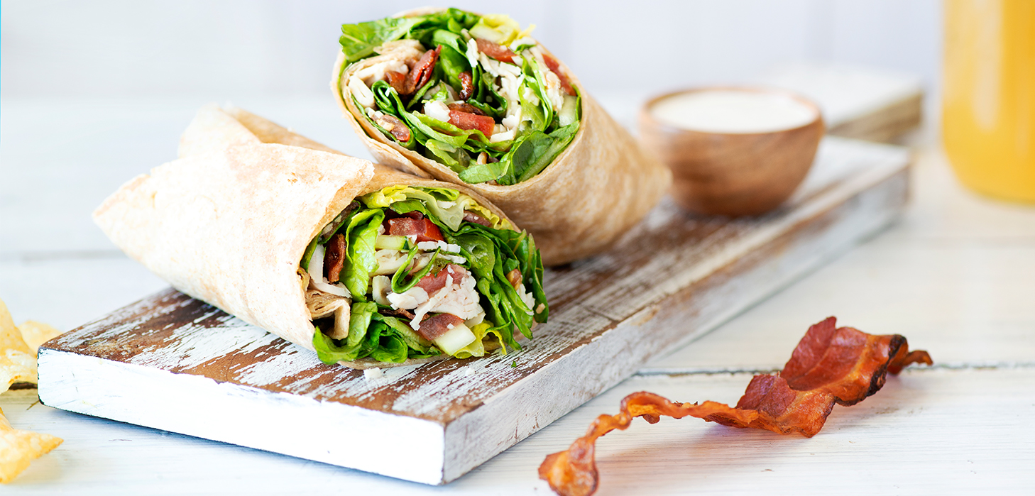 a chicken bacon wrap on a wooden cooking board with a slice of bacon next to it