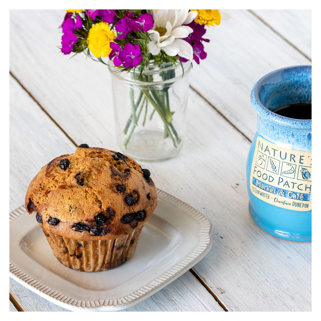 Blueberry Muffin in a white little plate next to Nature's Food Patch Vase and behind a flowers banch in a clear jar