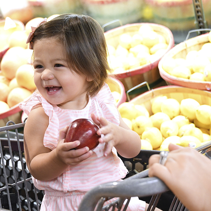 a baby girl holding a apple in her hands