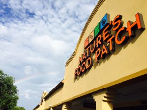 Nature's Food Patch storefront in Clearwater Florida with rainbow over it.