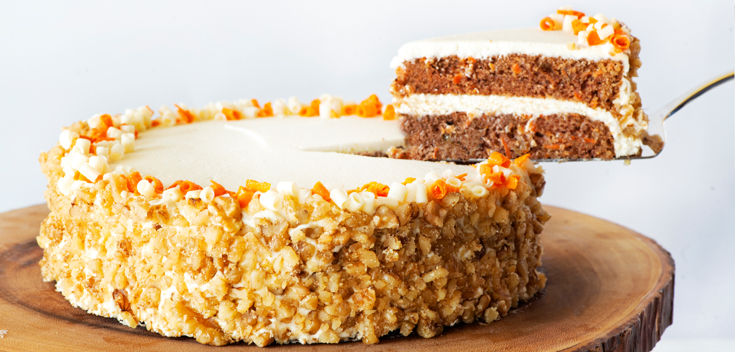 Carrot Cake on a wooden cake stand with slice on a flat cake server